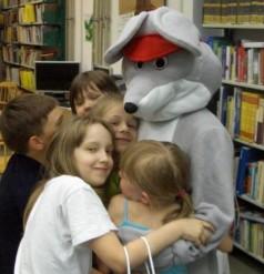 zdjęcie na którym dzieci tulą się do Myszki Norki